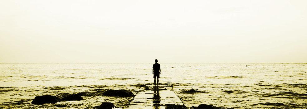 Una persona mirando al horizonte marino
